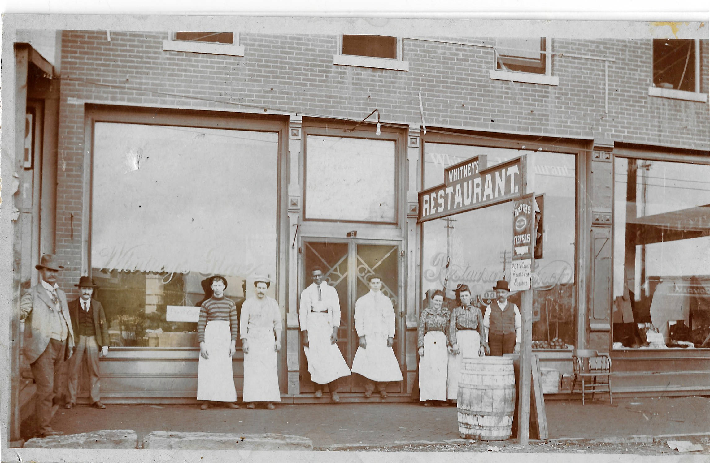 Photograph of Tom Buffington (far left), Chief of the Cherokees and Mayor of Vinita, along with restaurant employees, standing in front of Whitney's Restaurant, in downtown Vinita, Oklahoma, circa 1910
