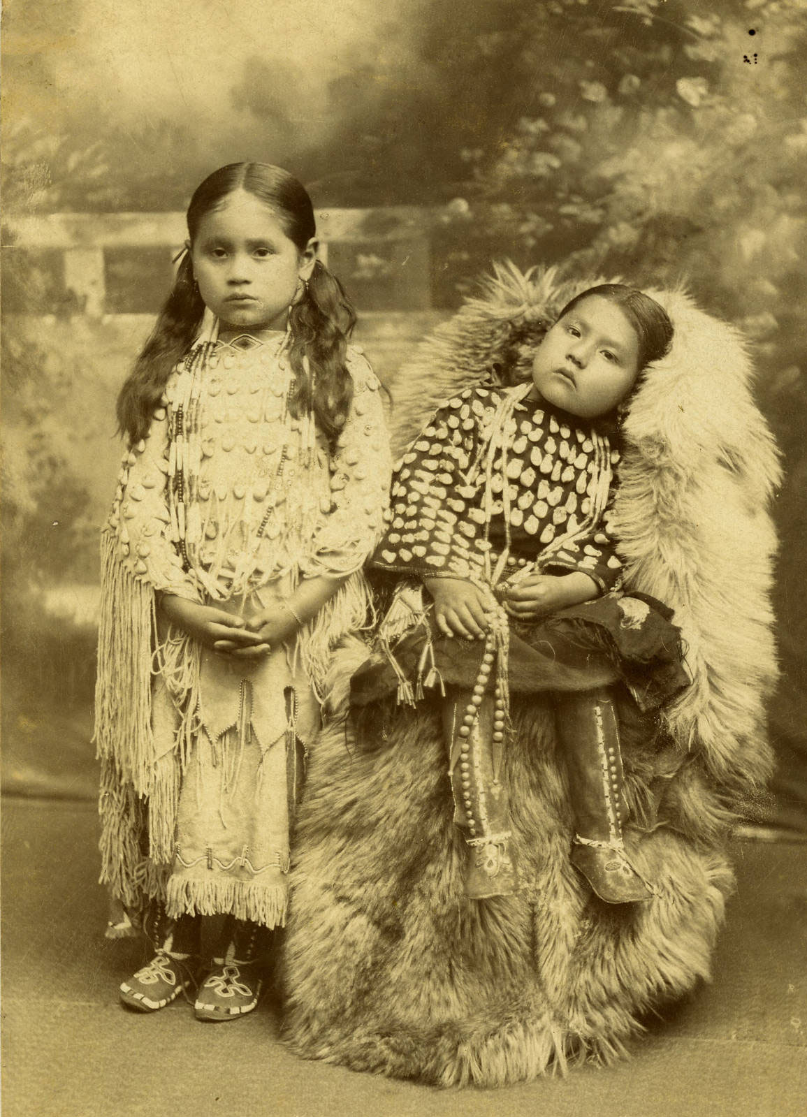 Cabinet card photograph of two Kiowa girls, leather dresses adorned with elk's teeth, Chickasha, Oklahoma, Indian Territory, circa 1892-1906